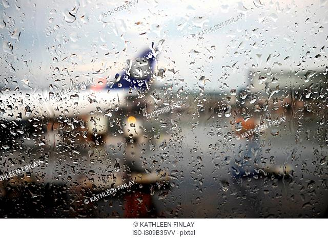 Window view of airplane parked in airport apron in rain