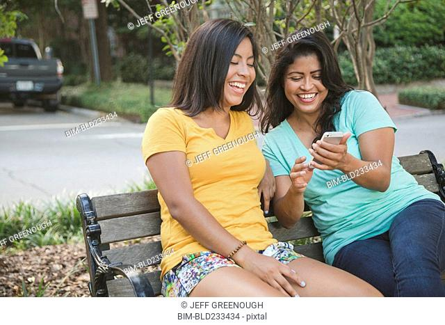 Hispanic mother and daughter using cell phone on park bench
