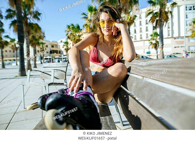 Young woman with inline skates wearing sunglasses sitting on a bench