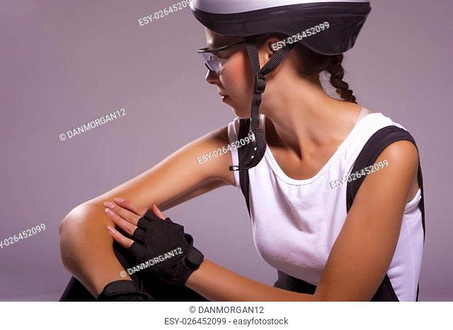 natural portrait of professional female caucasian bike athlete sitting and thinking. horizontal image