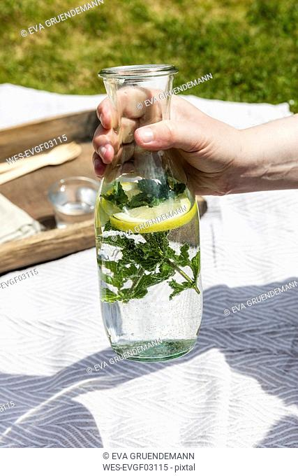 Hand holding carafe with flavored mint water over picnic blanket