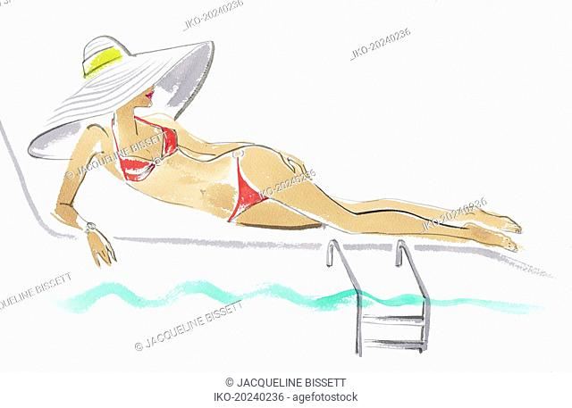 Woman wearing large sun hat reclining on sun lounger beside swimming pool