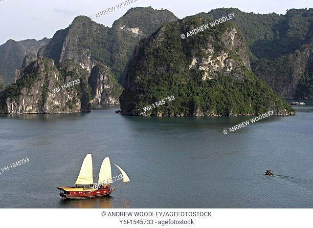 Cruising junk with sails hoisted Halong Bay Vietnam
