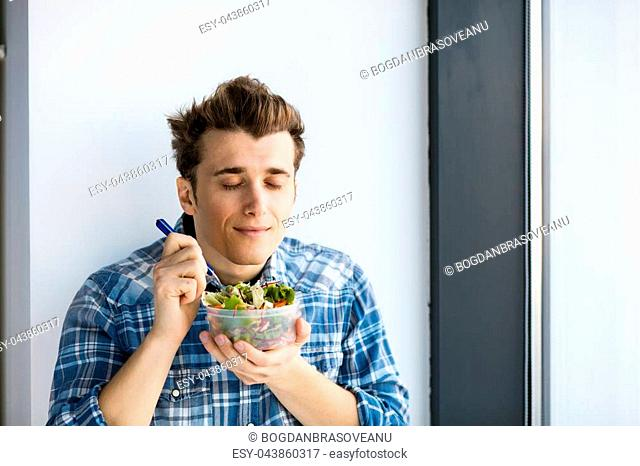 young man eating his vegan salad from a plastic box, his take away lunch at work