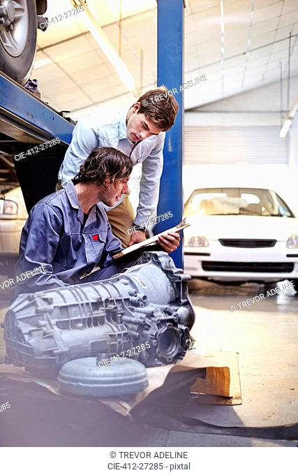 Mechanic with clipboard talking to customer in auto repair shop