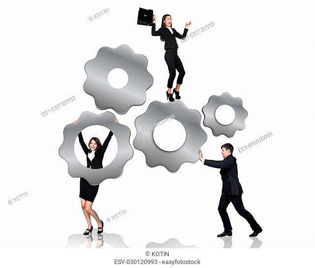 Businessman pushes metal gears , woman hangs on them, isolated on the white background