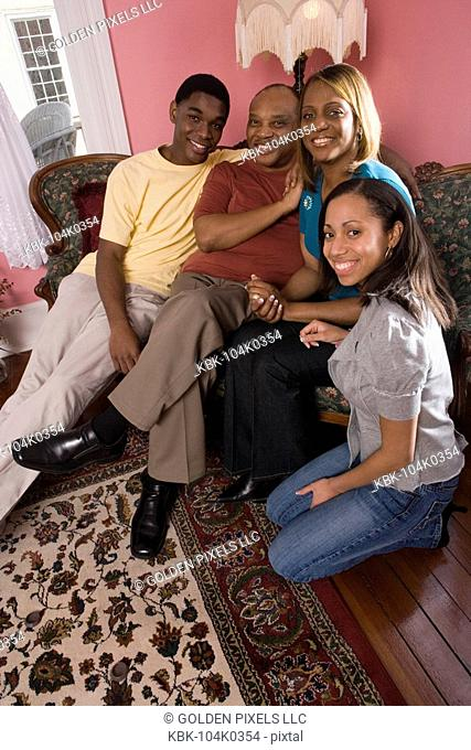Cheerful family in living room looking at photo album