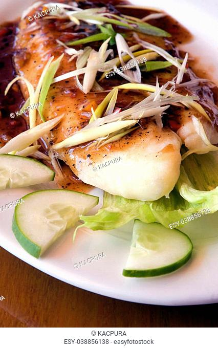 A fresh fish and green onions dish on a white china plate