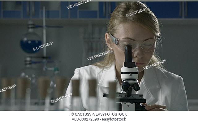Lab technician doing microscope sample analysis