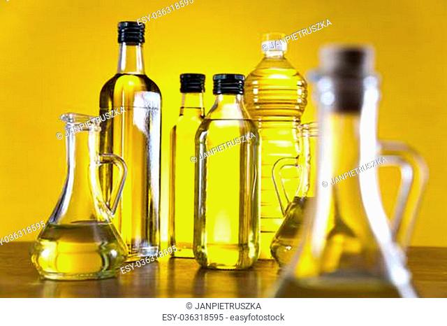 Glass bottles of premium virgin olive oil isolated on a yellow background