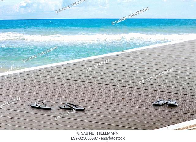 black sandals on a boat dock on a boardwalk at see..im background the blue sea