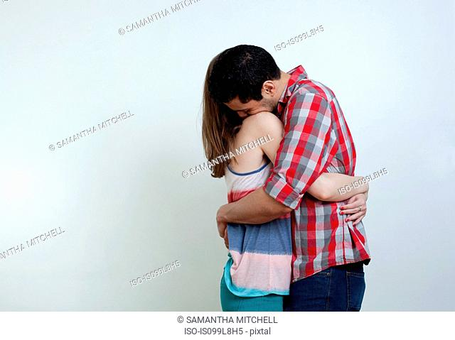 Young couple embracing, studio shot