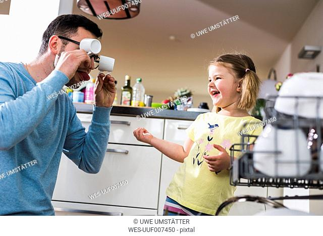 Playful daughter and father clearing dishwasher