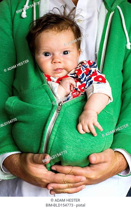 Caucasian father holding baby girl in zipped hoodie