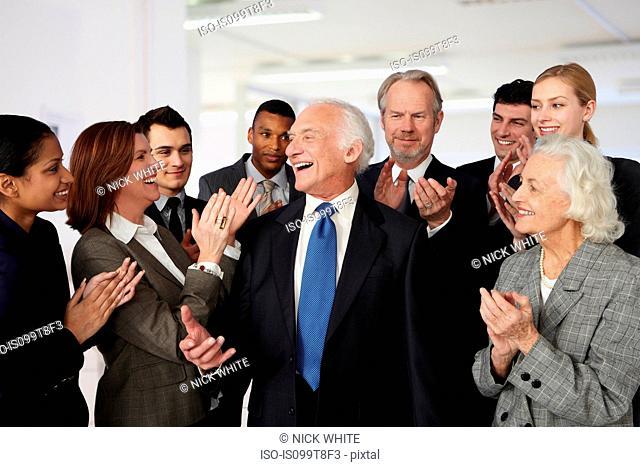Colleagues congratulating businessman