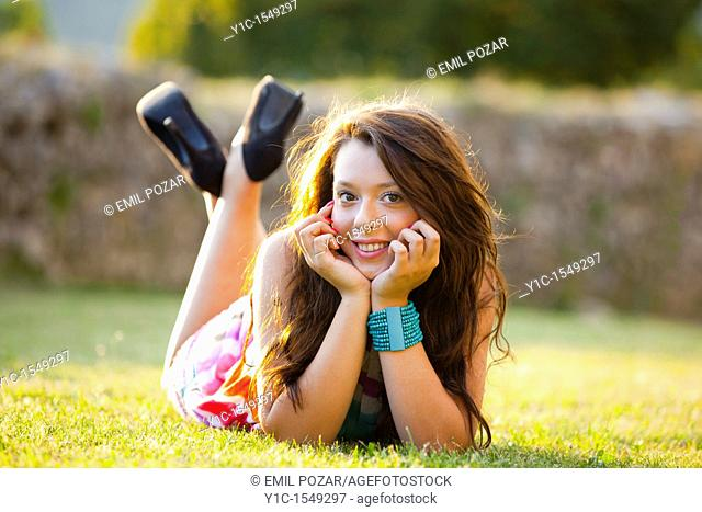 Lying on a grass and smiling young teen woman