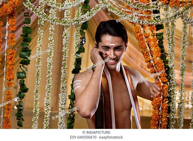 Smiling groom talking on cell phone