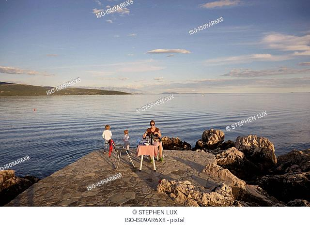Mother and two sons picnicing on coast, Krk, Croatia