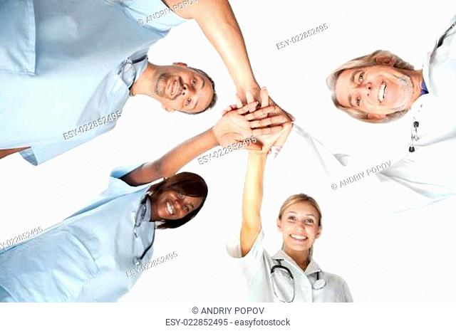 Group of doctors joining hands with low angle view