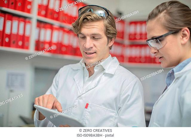 Two workers in thread factory, looking at digital tablet