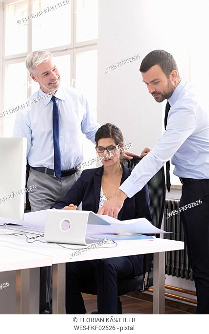 Colleagues standing in office, discussing blueprints