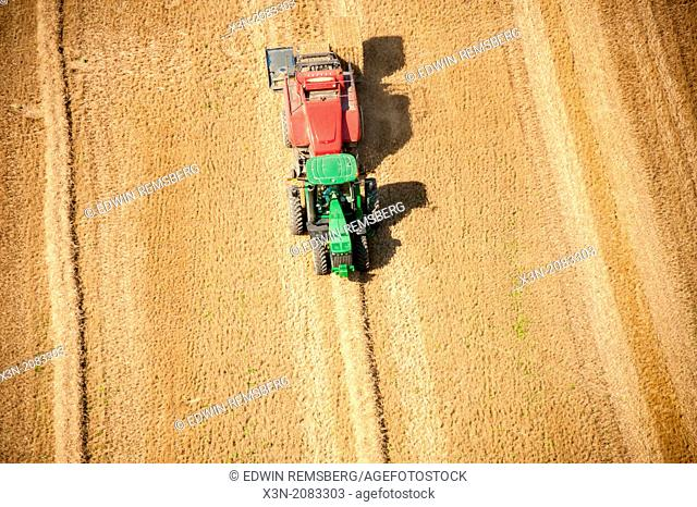 Aerial photos farmer baling large square bales of straw on the Eastern Shore of Maryland USA