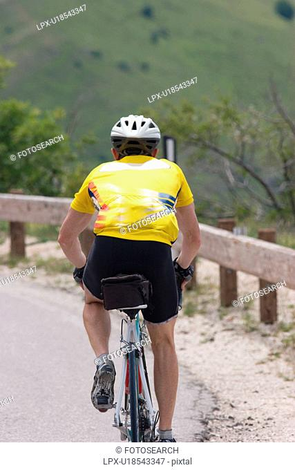 Rear view of cyclist in yellow shirt, black shorts, cycling up mountain on winding road in morning sun , Umbria, Italy, with green fields and trees in...