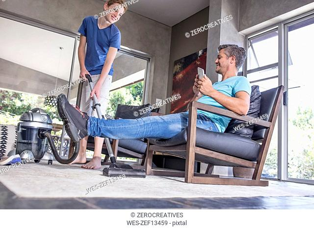 Father relaxing while son vacuuming in living room