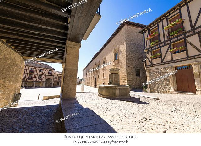 arcade of street with fountain in Penaranda de Duero village, with Palace of the Counts of Miranda, in Burgos, Castile and Leon, Spain, Europe