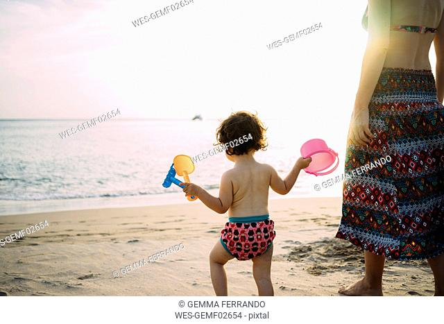 Thailand, Koh Lanta, back view of baby girl with toys on the beach by sunset