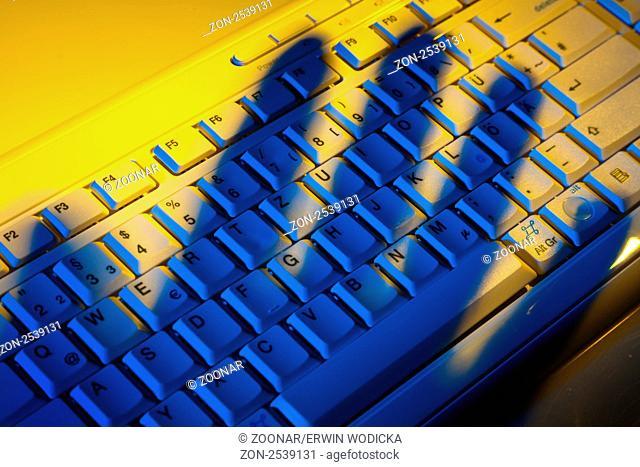 Computertastatur und Schatten einer Hand. Diebstahl von Daten