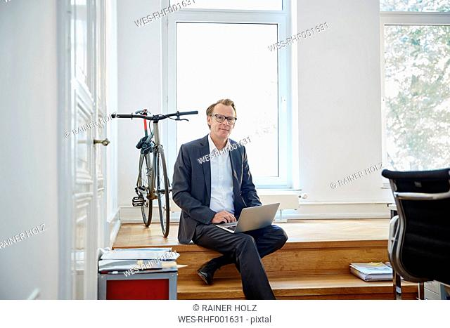 Businessman with laptop sitting on steps in an office