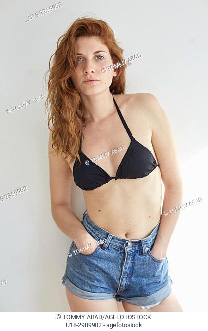 Three quarter length portrait of young redhead woman wearing black bikini and shorts, looking at camera