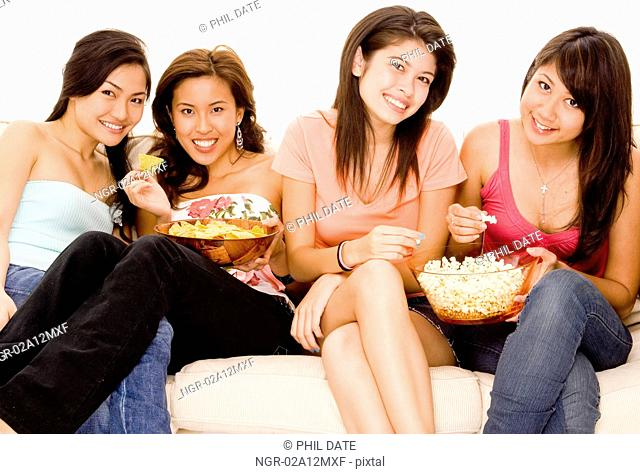 Three young women and a teenage girl sitting on a couch and eating snacks