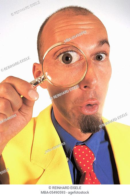 man at amazed expression keeps loupe in front of the eye