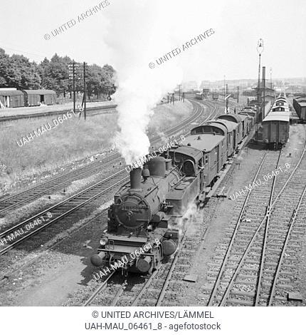 Ein Güterzug, gezogen von einer Dampflokomotive der Baureihe 31, verläßt einen kleinen Bahnhof, Deutschland 1930er Jahre