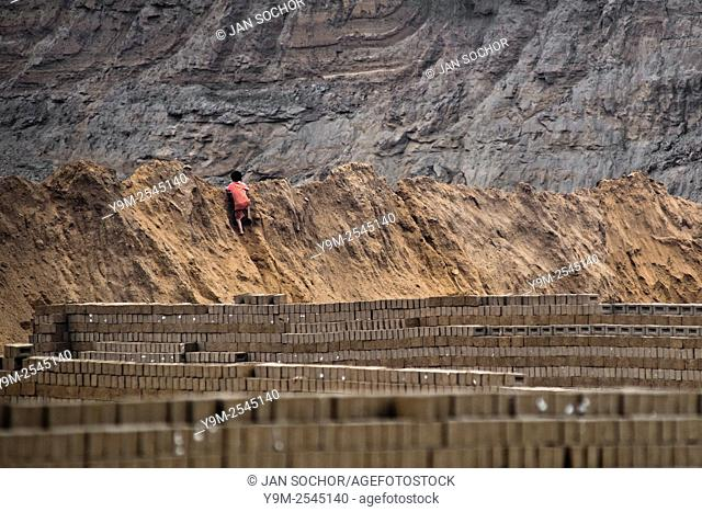 A Peruvian boy climbs the heap of mud while working at a brick factory in Huachipa, a suburb in the outskirts of Lima, Peru, 10 August 2012