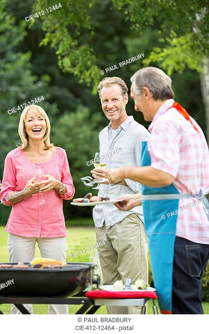 Family standing at barbecue in backyard