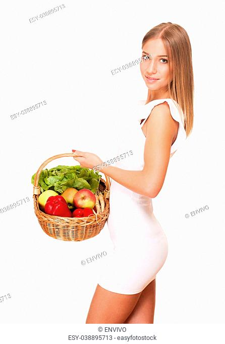 Fit gorgeous young blond woman holding wicker basket full of fresh vegetables