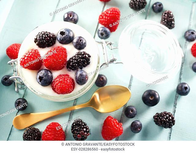 Jar of yogurt with blueberries, blackberries and raspberries on wooden tray