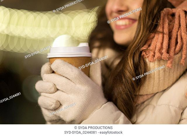 happy woman with coffee over christmas lights