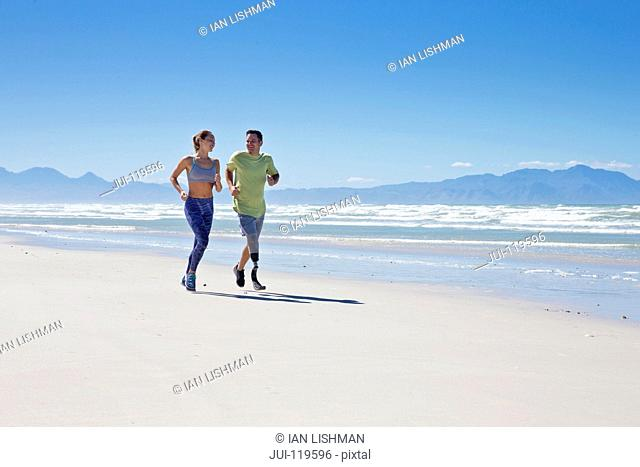 Man Wearing Prosthetic Blade Running Along Shoreline Of Beach With Female Partner