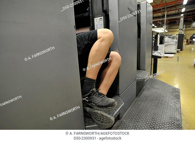 Mechanic working on an industrial printing machine, legs, Västeras, Sweden