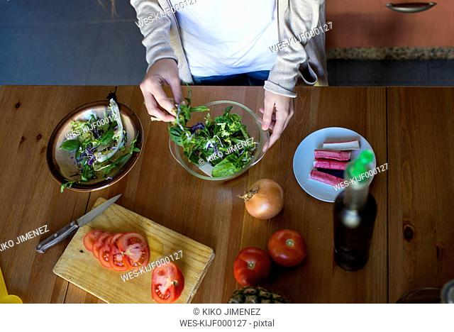Young woman making a salad in the kitchen