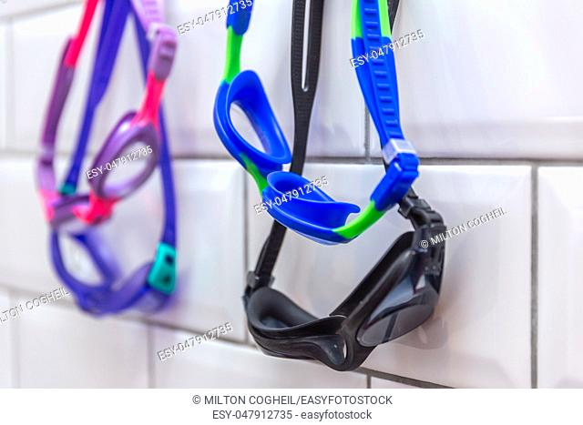 Family of swimming goggles hanging on a tiled wall