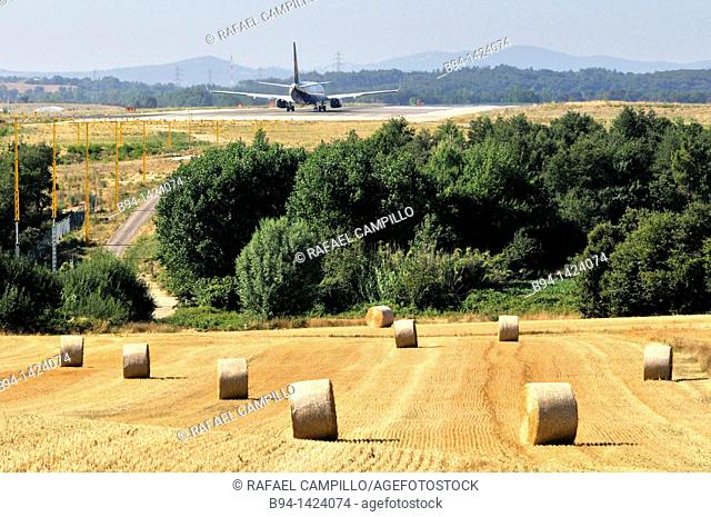 Plane and straw rolls. Girona-Costa Brava Airport, at 12.5 km southwest of the city of Girona, next to the small village of Vilobí d'Onyar. Girona