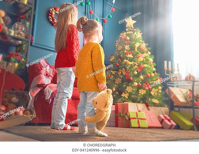 Merry Christmas and Happy Holidays! Cheerful cute little children girls. Kids sisters near tree indoors