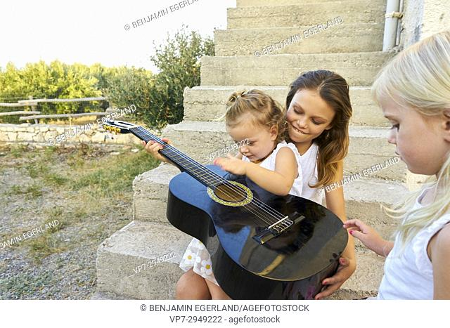 siblings playing together with guitar outside in garden. Australian ethnicity. During holiday stay in Hersonissos, Crete, Greece
