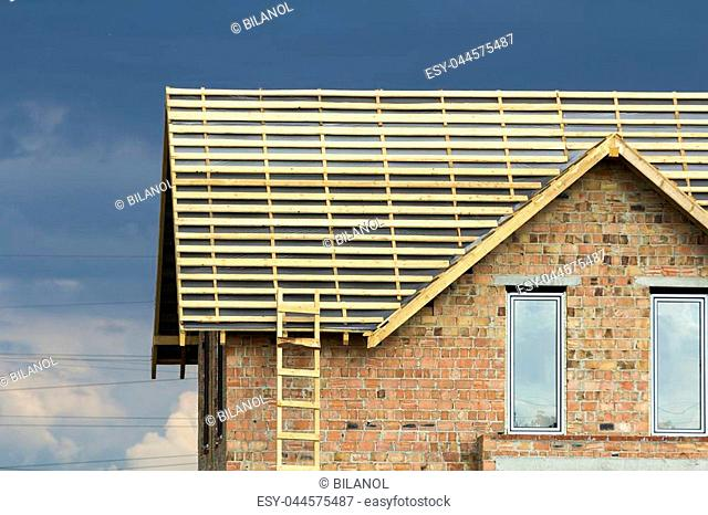 Close-up detail of new brick house top with two narrow plastic attic windows and wooden roof frame under construction on dark blue sky background