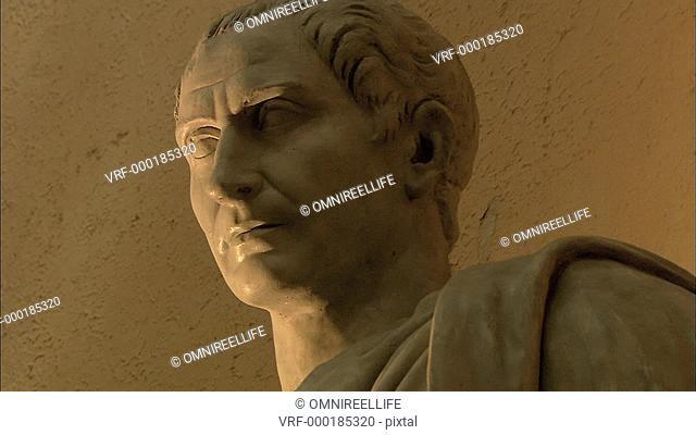 Marble statue of Julius Caesar with shadow on wall behind